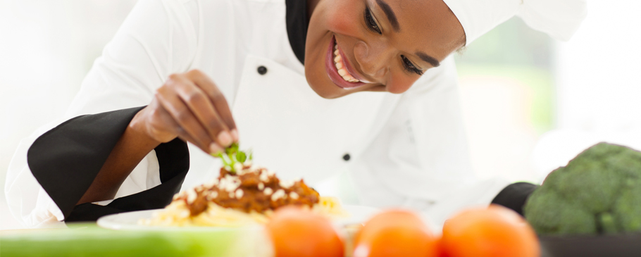 Smiling Chef Completing a Dish